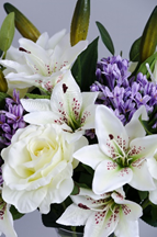 An image of an artificial flower bouquet containing white lilies and roses.