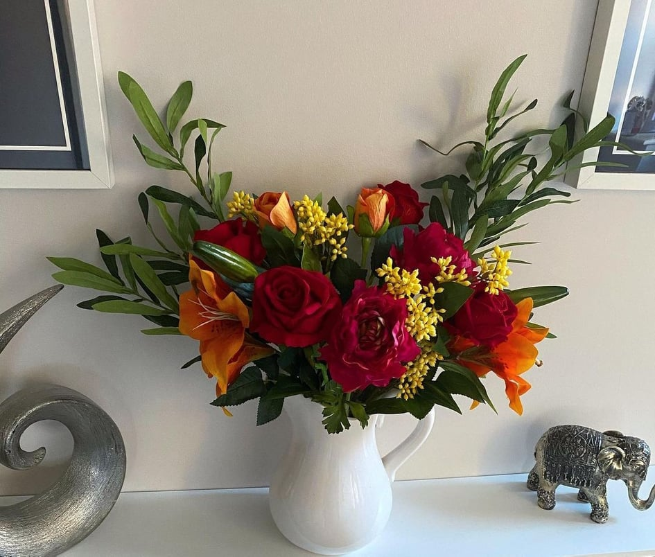 Styling artificial flowers in a vase.